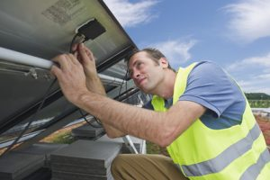 Germany, Munich, Technician fixing cable of solar panel